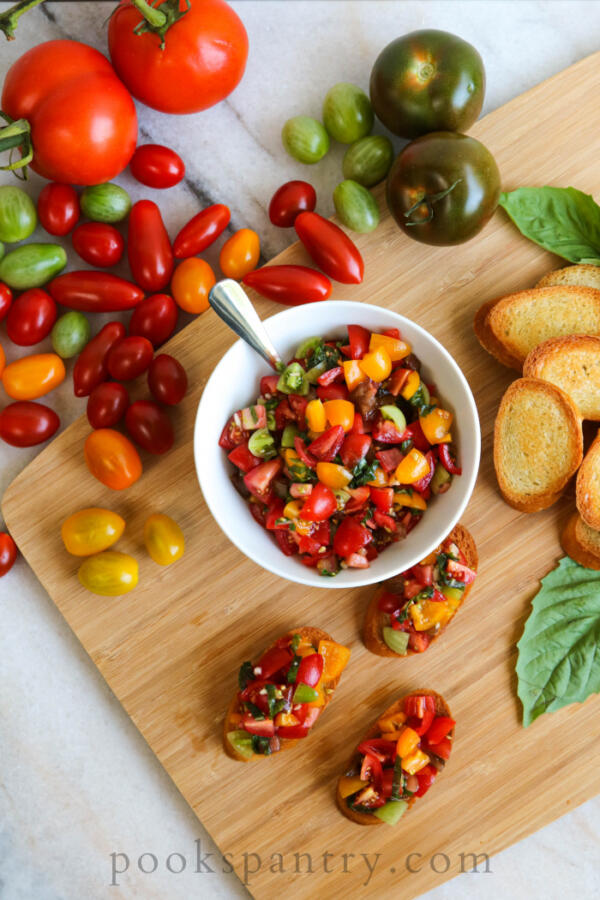 heirloom tomato bruschetta in white bowl with crostini and tomatoes