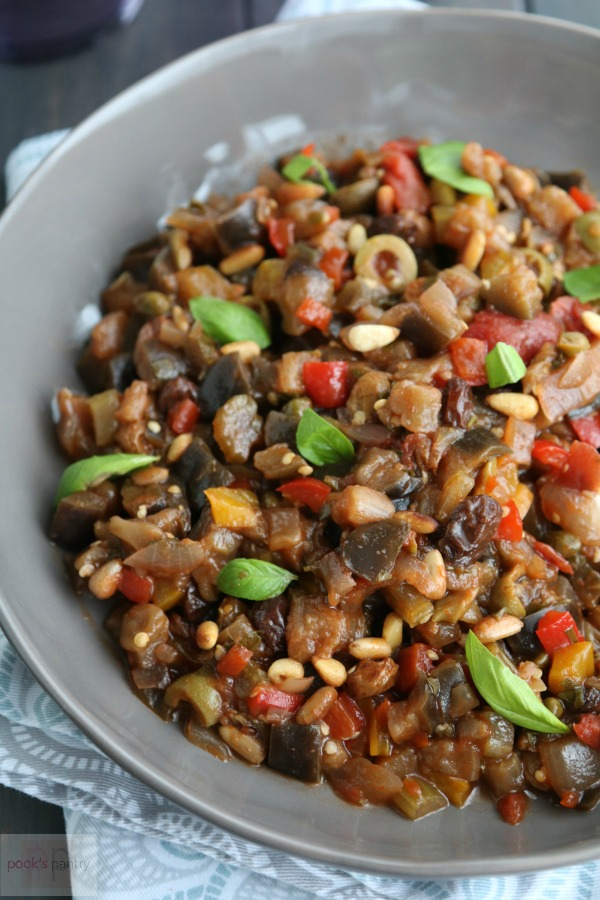 bowl of eggplant caponata with basil leaves and pine nuts