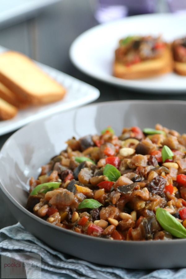 Eggplant caponata in shallow gray bowl with basil leaves