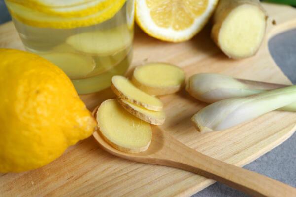 Ginger, lemongrass and lemons for cocktail on wooden board.