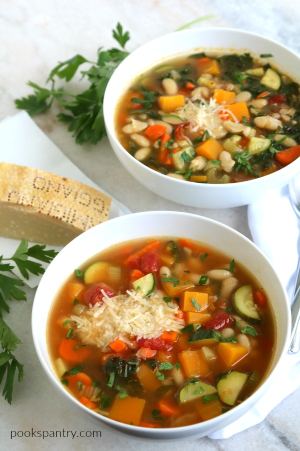 bowls of autumn minestrone soup with parmesan cheese rind