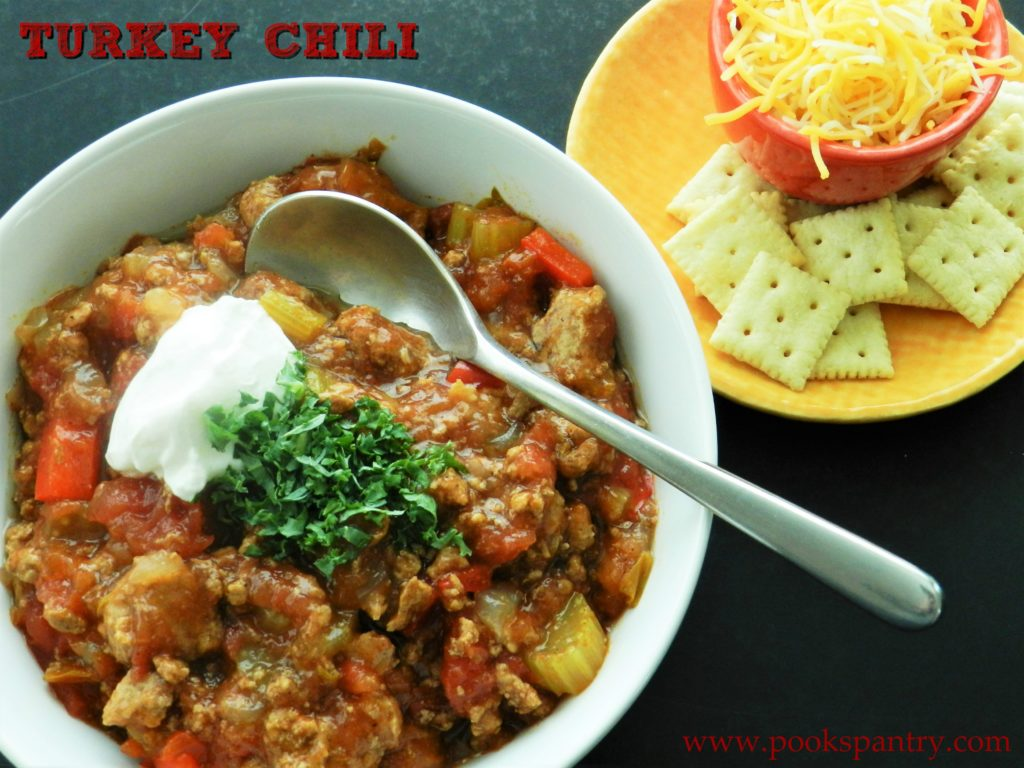 turkey chili in white bowl with sour cream