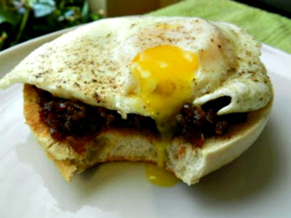 bacon jam on bagel with runny egg on top
