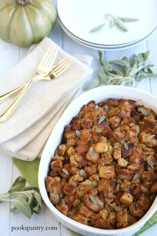 bread stuffing in white casserole dish with sage leaves