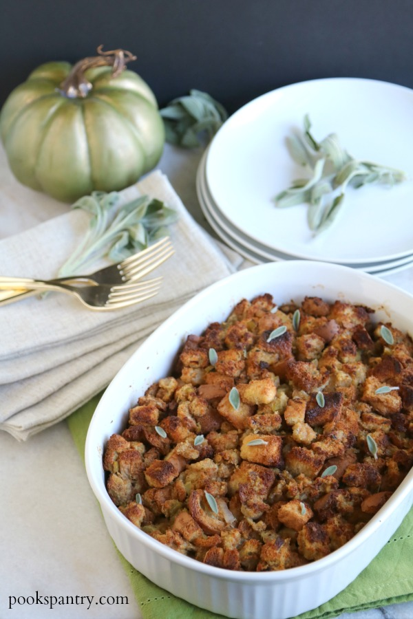 stuffing in white casserole dish with sage leaves