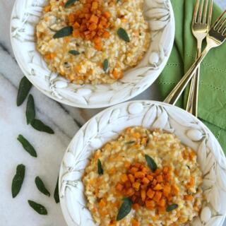 two bowls of butternut squash risotto with gold forks