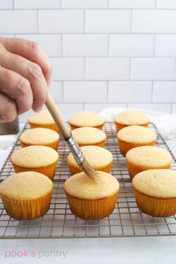 Brushing simple syrup onto ginger cupcakes.