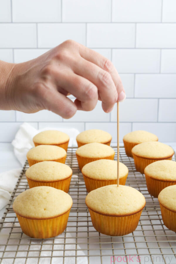 Poking holes into ginger cupcakes.
