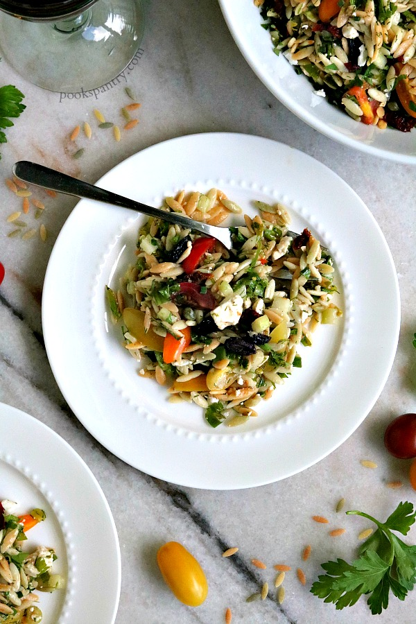 overhead of orzo salad with tomatoes and parsley