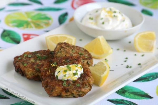 zucchini cakes on platter with lemon wedges