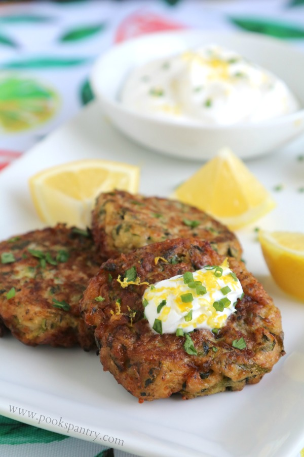 zucchini fritters on white platter with sour cream