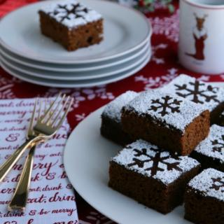 gingerbread cake recipe on platter with stacked plates in background