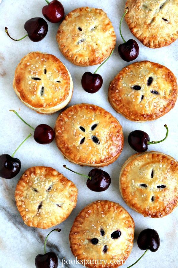 overhead shot of cherry hand pies with fresh cherries