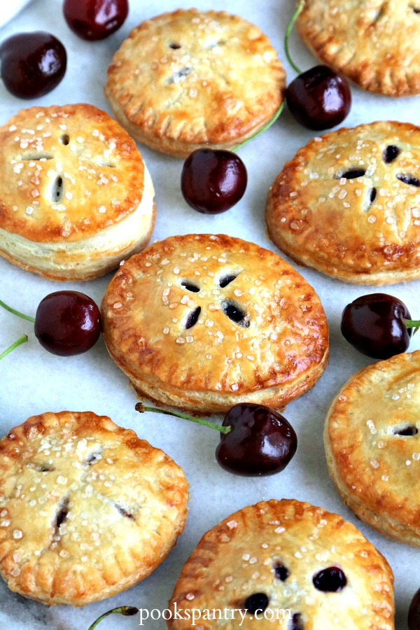 cherry hand pies on white background with fresh cherries