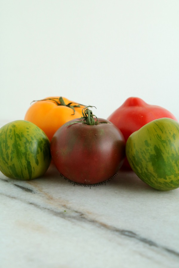5 heirloom tomatoes on marble board