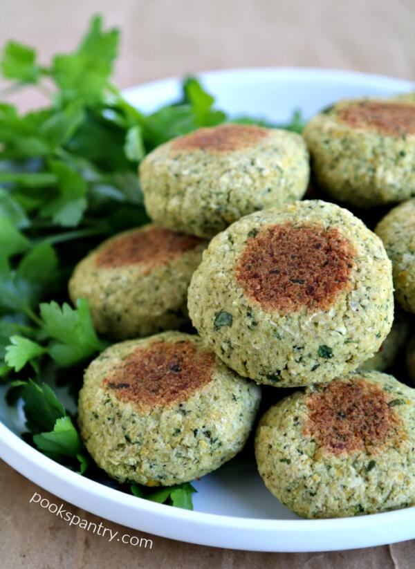 stacked falafel on white plate with parsley