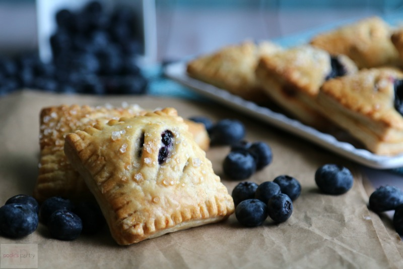 Blueberry Mini Pies on brown paper with blueberries