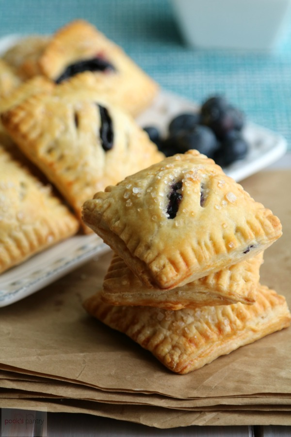 stack of blueberry mini pies on brown paper