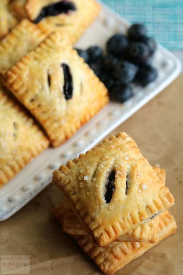blueberry hand pies on brown paper with white plate
