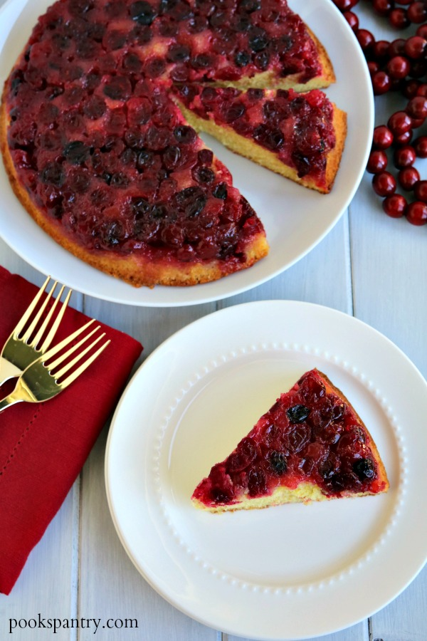 slice of cranberry orange upside down cake on white plate with sliced cake