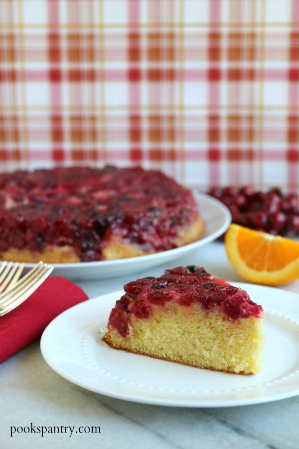 upside down cake on white plate with orange slice and cake in background