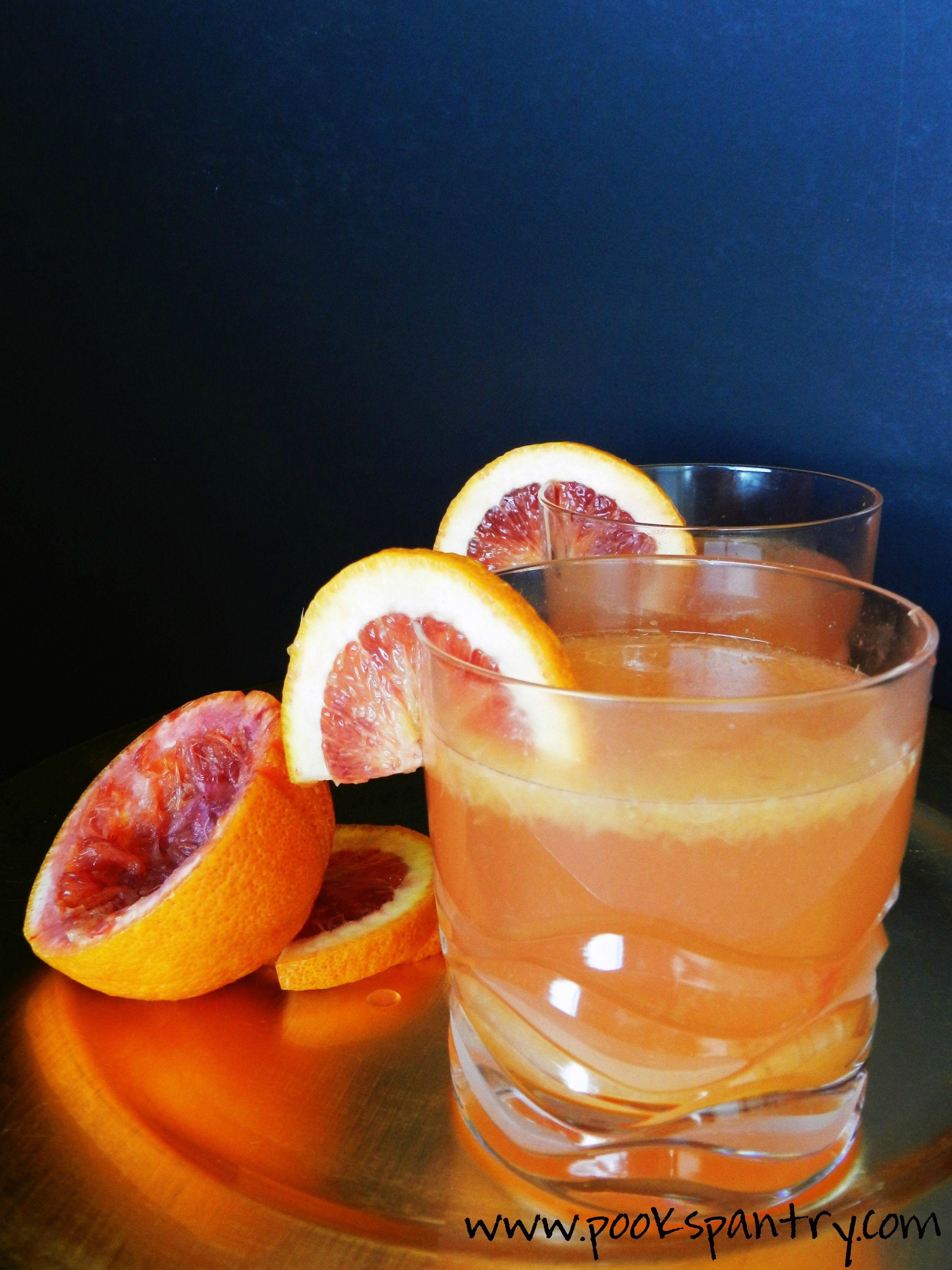 blood orange white wine spritzer on gold tray