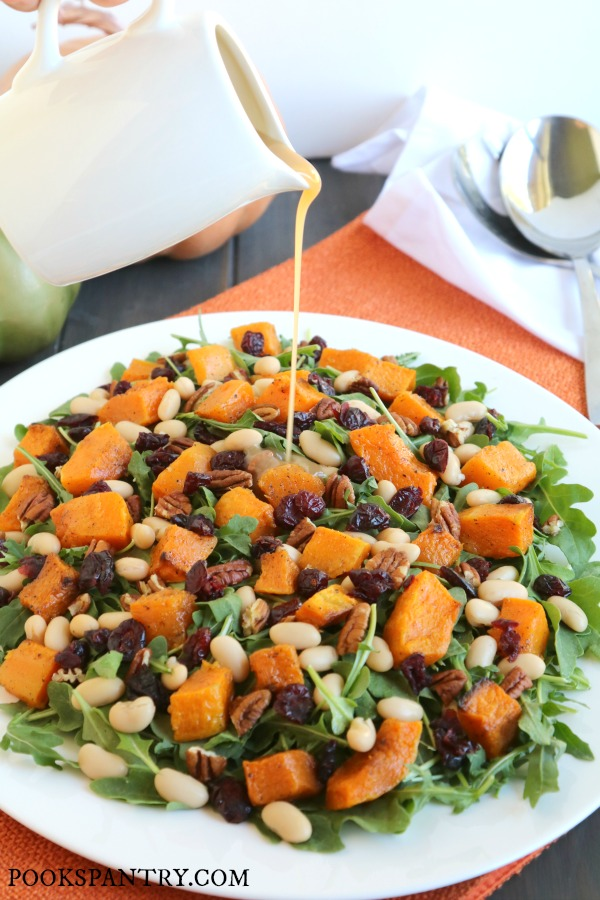 pouring dressing on butternut squash arugula salad