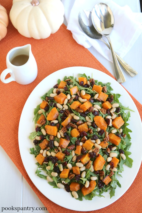 arugula salad with butternut squash on white platter with dressing and serving spoons