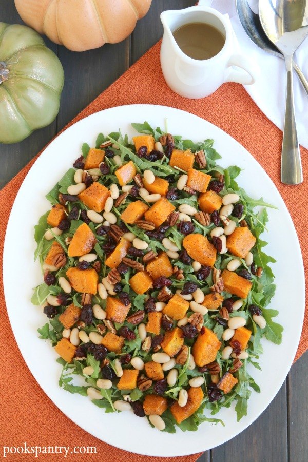 Overhead photo of butternut squash arugula salad on white platter