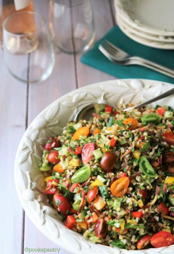 big bowl of grain salad with wine glasses
