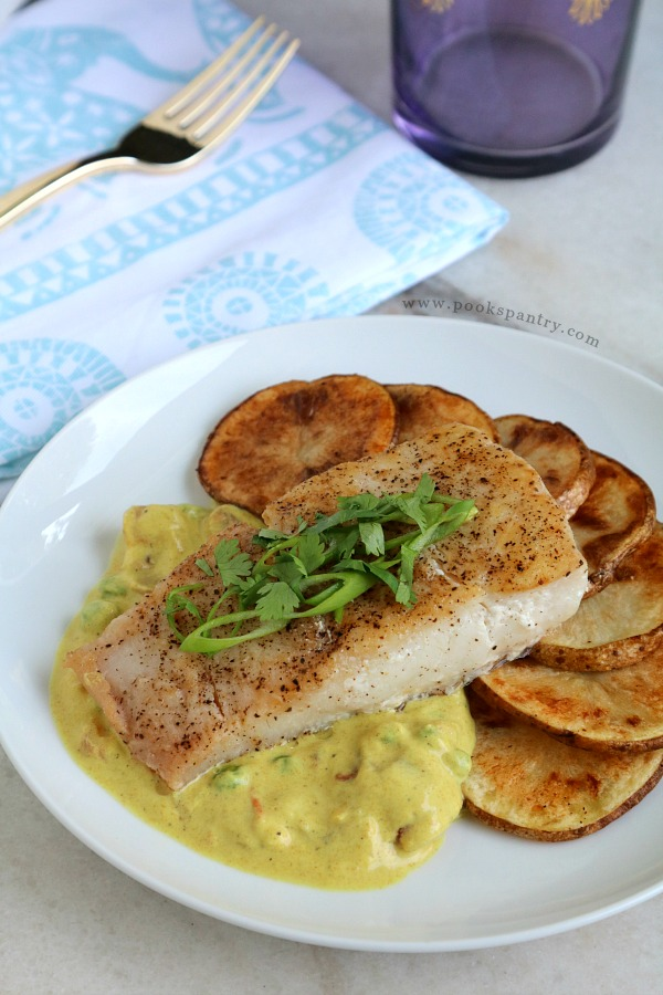 coconut curry corvina recipe with sliced potatoes on white plate