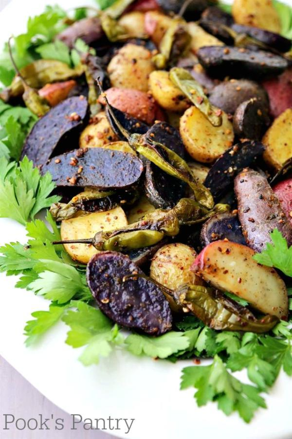 togarashi spiced roasted fingerling potatoes with shishito peppers on white platter