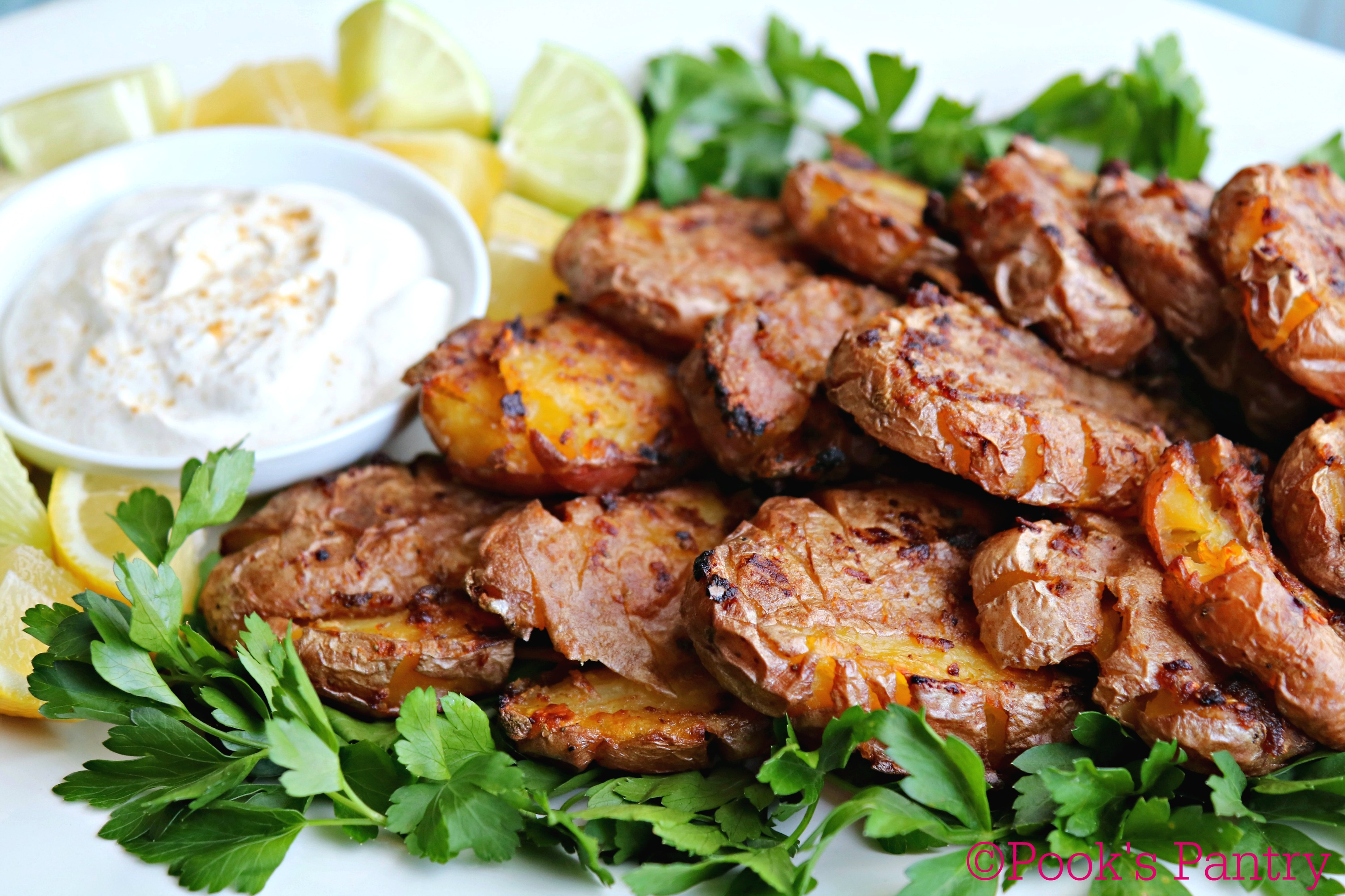 potatoes with sour cream, lemon and parsley on white platter