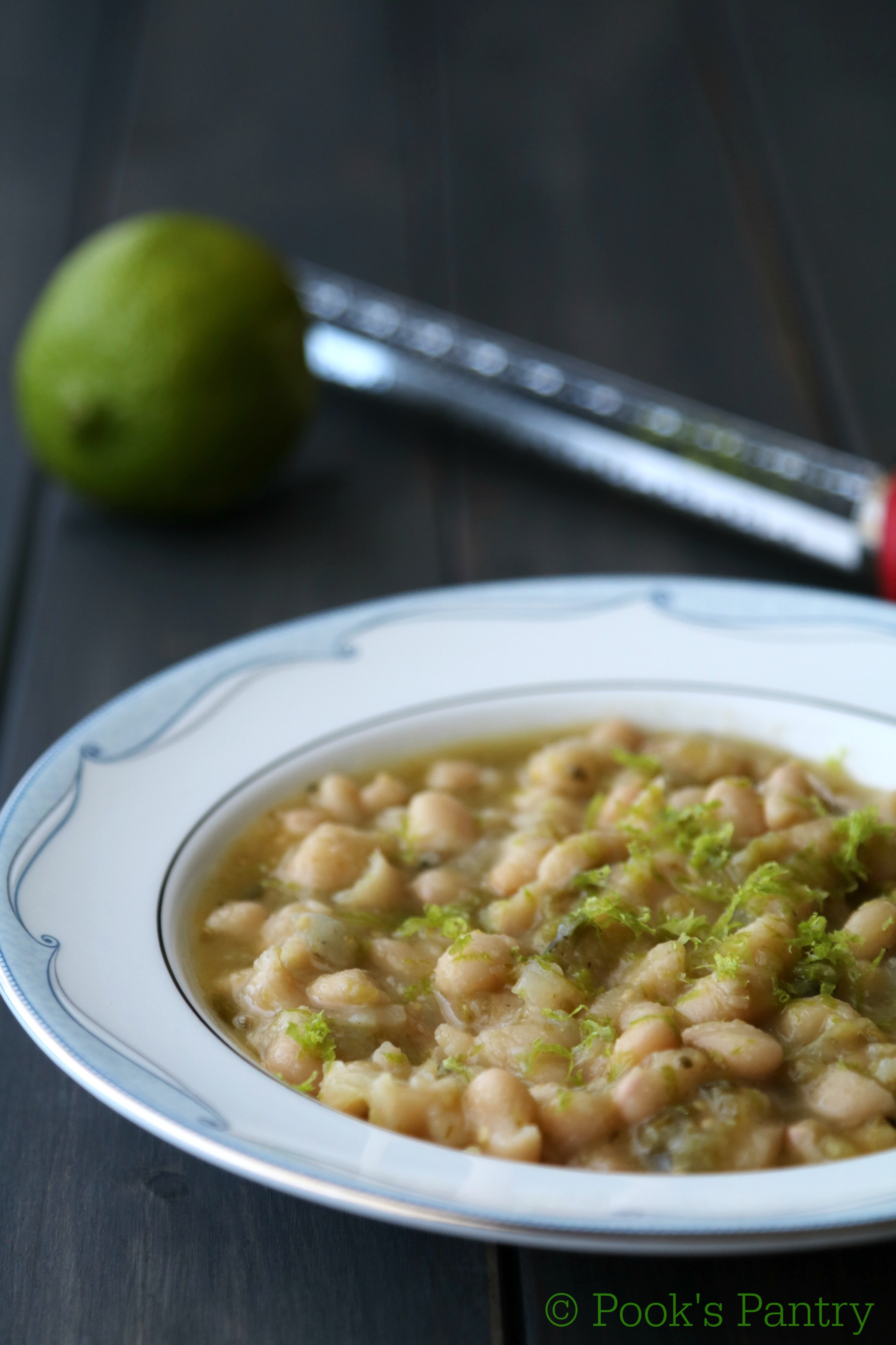 White Beans in blue and white shallow bowl with lime