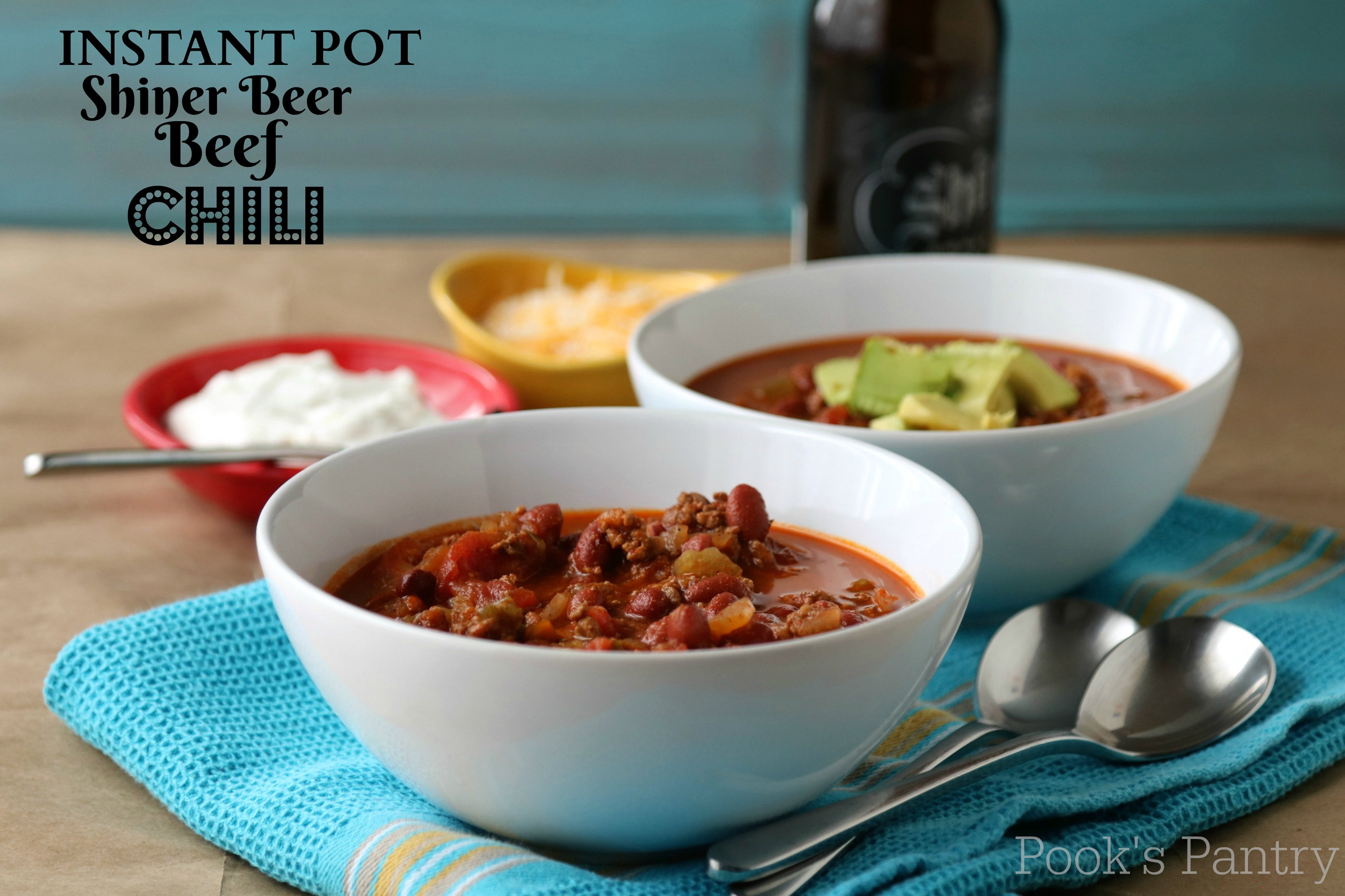 beef and beer chili in white bowl with spoons on blue kitchen towel