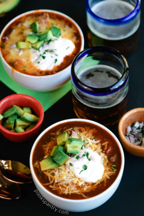 bowls of instant pot beer chili with glasses of beer