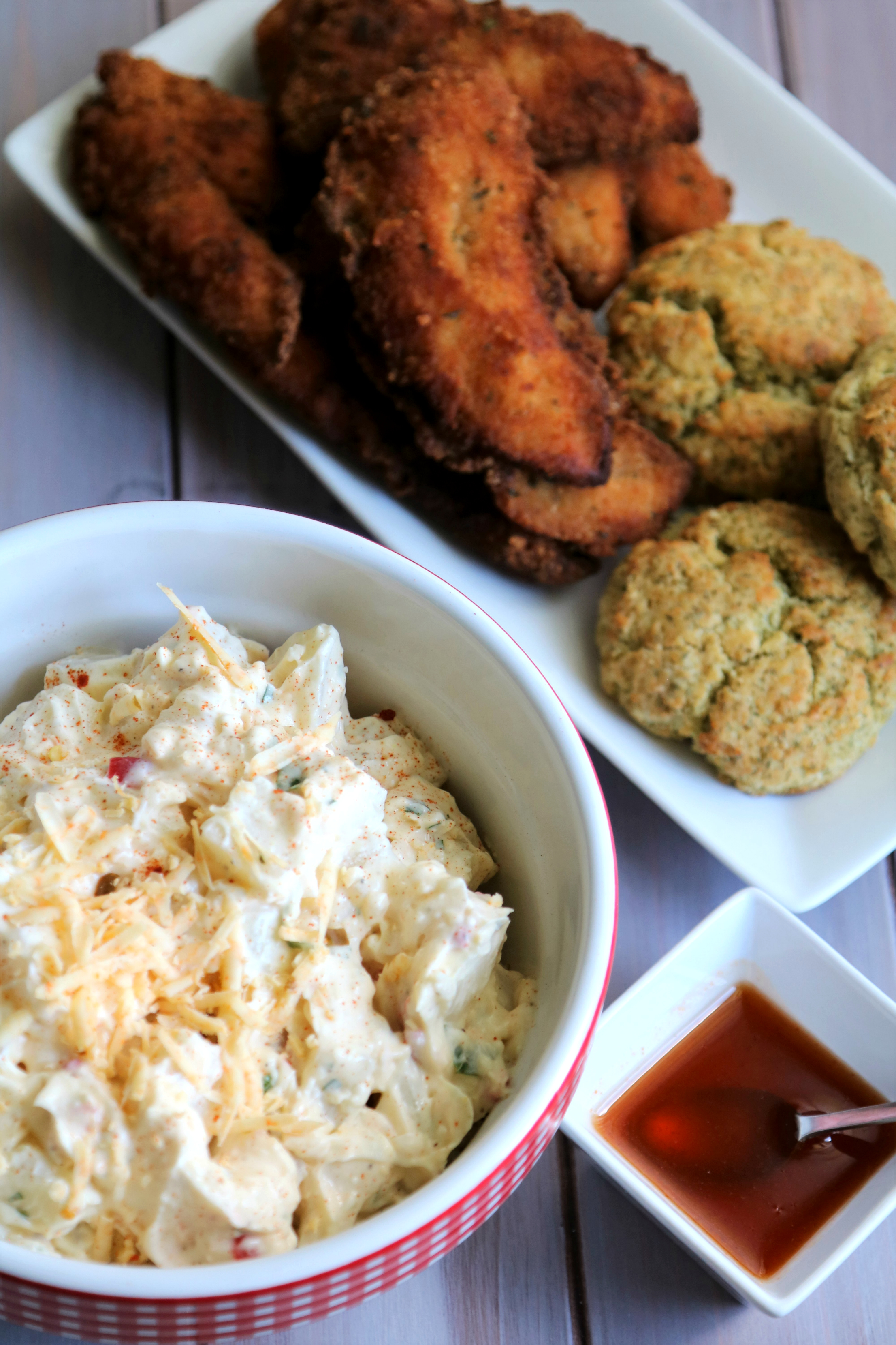 pimento cheese potato salad with crispy chicken tenders and potato dill biscuits on white platter