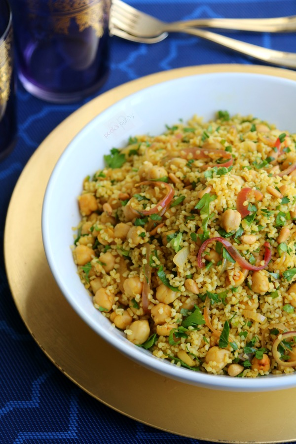 bulgur wheat salad with red onions and chickpeas in white bowl with gold charger plate