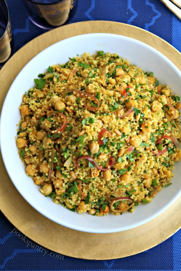 bulgur with chickpeas in white bowl with gold charger plate