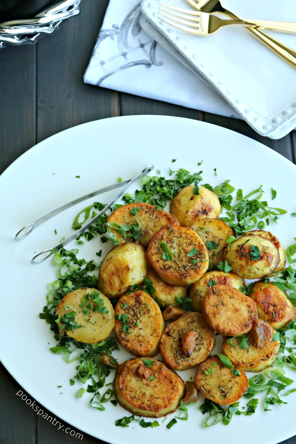 melting potatoes with garlic and herbs on white platter