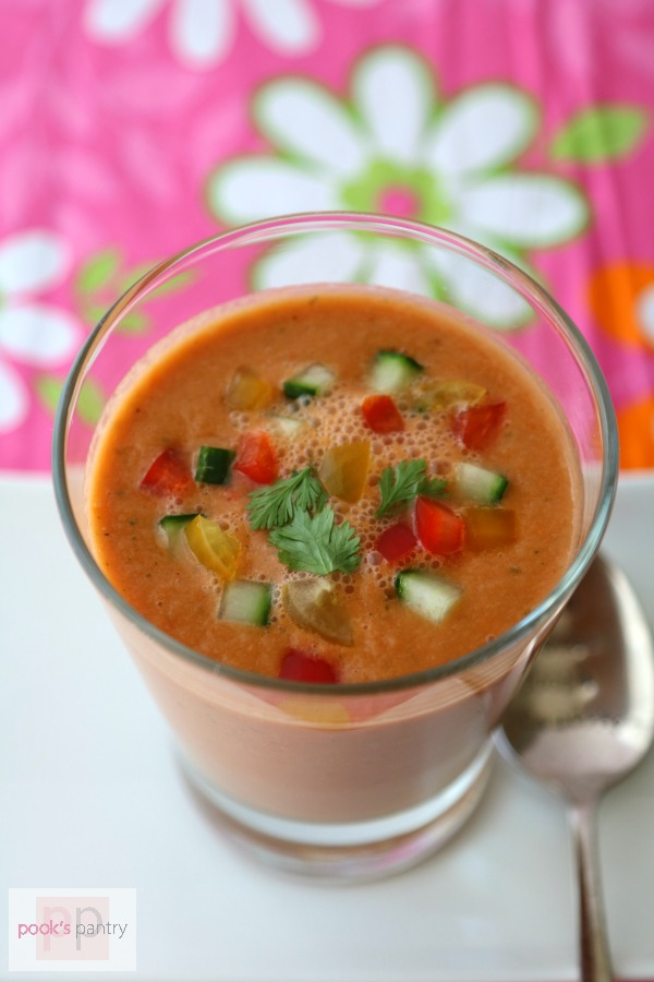 Glass of watermelon gazpacho with diced vegetables and cilantro.