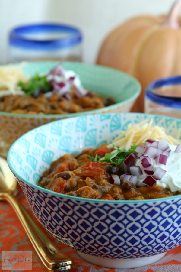 turkey pumpkin chili in blue and white bowl with gold spoon
