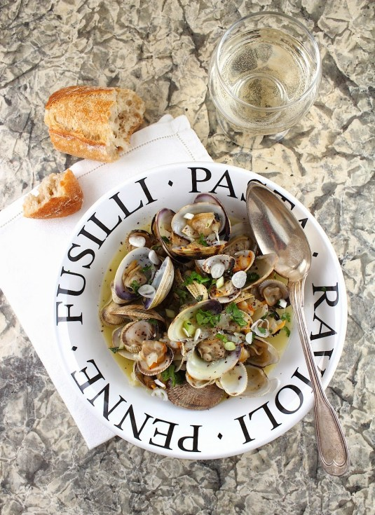 clams in white bowl with writing and piece of baguette