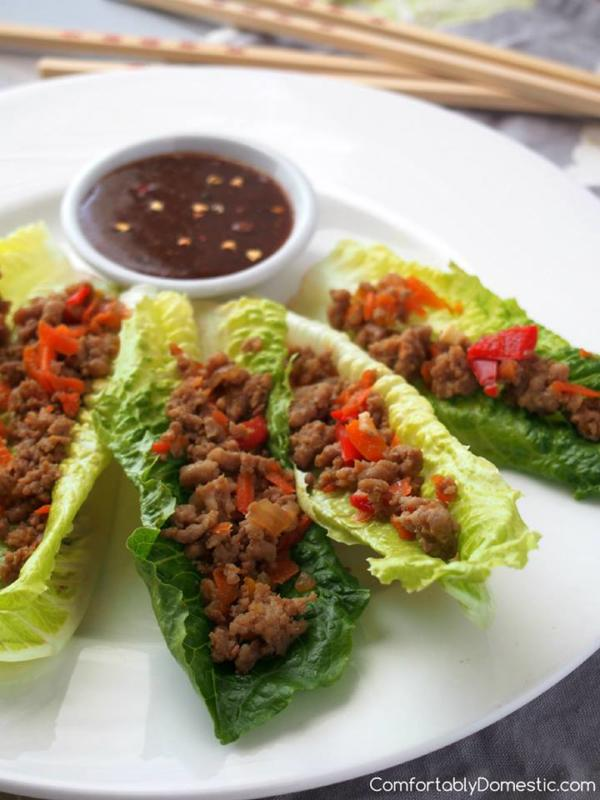 turkey lettuce wraps on white plate with bowl of sauce