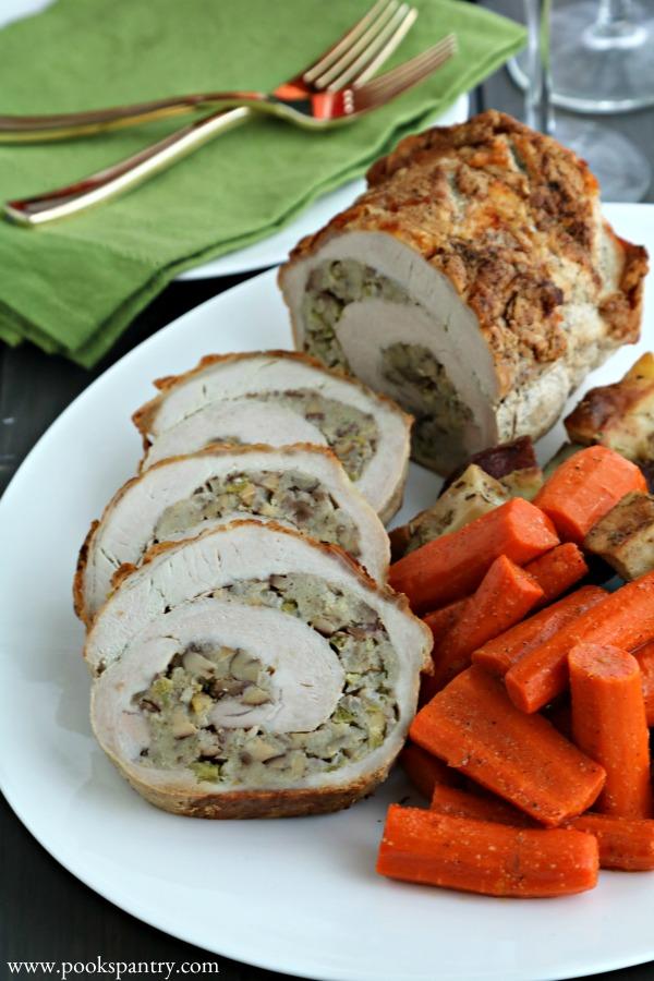 stuffed pork loin roast on white platter with carrots