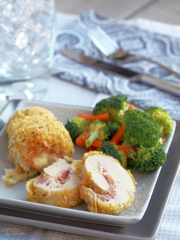 chicken cordon bleu with broccoli on white plate