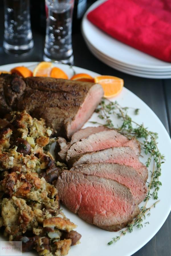 Beef tenderloin on white platter with chestnut stuffing