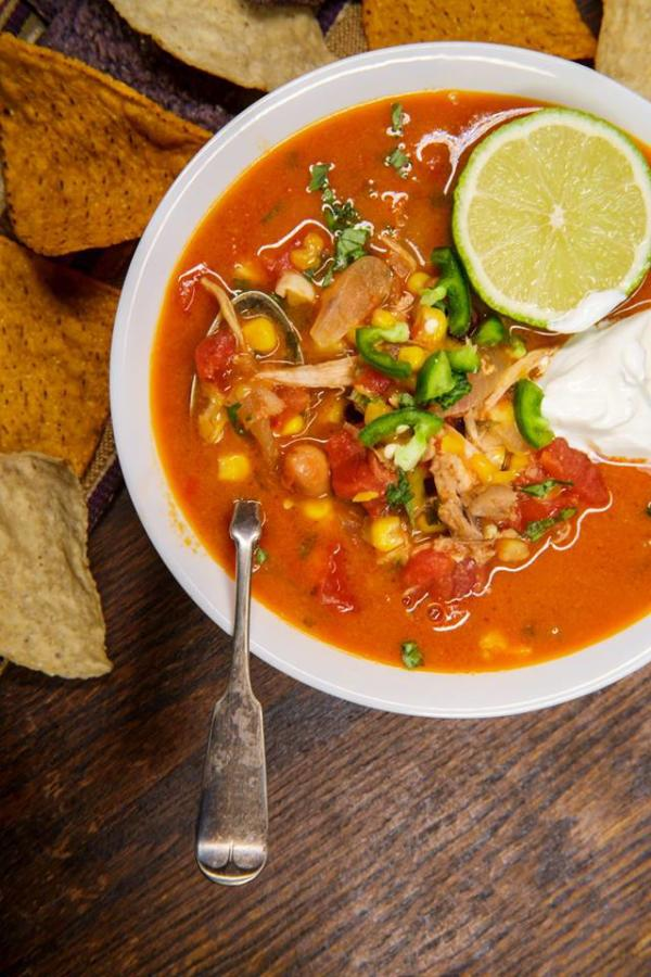 bowl of chicken tortilla soup on wood background