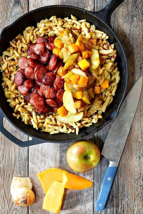 sausage, apples and butternut in cast iron pan with knife, cheese and apple