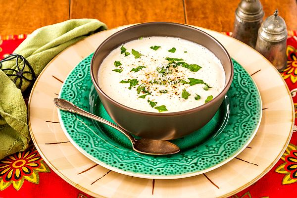 cream of cauliflower soup in green bowl on green plate with red placemat